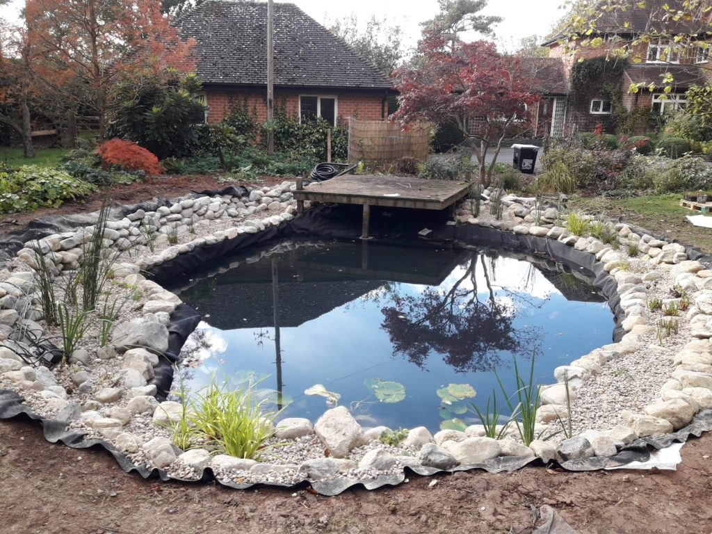 Completed swim pond with boulders and cobble stone