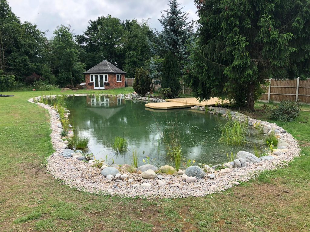 Completed swim pond with boulders and cobble stone with decking, overall pond