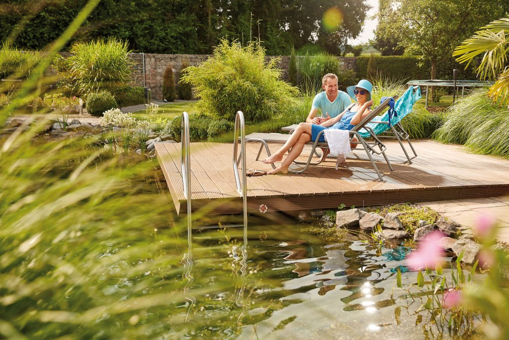 Homeowners enjoy their natural swimming pond with decking
